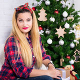 Young beautiful woman sitting in decorated room with Christmas t Royalty Free Stock Photo