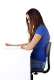 Young beautiful woman sitting by the desk and reading. Stock Photos