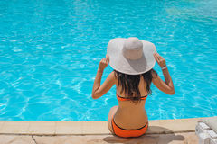 Young beautiful woman sitting on edge of the pool Stock Images