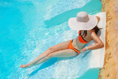 Young beautiful woman sitting on edge of the pool Royalty Free Stock Image