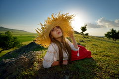 Young beautiful woman sitting on field in summer Stock Image