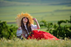 Young beautiful woman sitting on field in summer Stock Photo