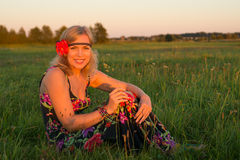 Young beautiful woman sitting in a field at sunset Royalty Free Stock Photo