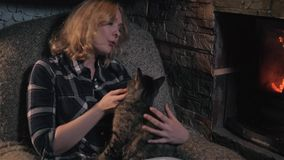 Young Beautiful Woman Sitting By Fireplace And Hugging Her Cute Cat In a Country House stock video
