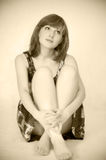 Young beautiful woman sitting on floor. Sepia toned Stock Photos