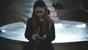 Young beautiful woman sitting on the fountain in the evening and using the smartphone, waiting somebody in city centre. stock video footage