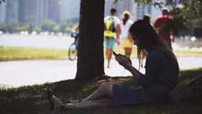 Young beautiful woman sitting on grass in park and using smartphone. Female resting in downtown of Chicago, USA.