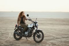 Young beautiful woman sitting on her old cafe racer motorcycle in desert at sunset or sunrise. Young beautiful woman sitting on her old cafe racer motorcycle in Stock Photo