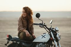 Young beautiful woman sitting on her old cafe racer motorcycle in desert at sunset or sunrise. Young beautiful woman sitting on her old cafe racer motorcycle in Royalty Free Stock Images