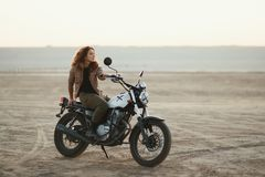 Young beautiful woman sitting on her old cafe racer motorcycle in desert at sunset or sunrise. Young beautiful woman sitting on her old cafe racer motorcycle in Stock Images