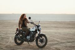 Young beautiful woman sitting on her old cafe racer motorcycle in desert at sunset or sunrise. Young beautiful woman sitting on her old cafe racer motorcycle in Royalty Free Stock Photos