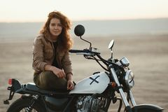 Young beautiful woman sitting on her old cafe racer motorcycle in desert at sunset or sunrise. Young beautiful woman sitting on her old cafe racer motorcycle in Royalty Free Stock Photography