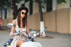 Young beautiful woman sitting on a italian scooter Royalty Free Stock Photos