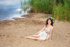 Young beautiful woman sitting at the lake shore Royalty Free Stock Images