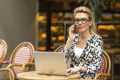 Young beautiful woman sitting with a laptop at an outdoor cafe. Royalty Free Stock Image
