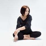 Young beautiful woman sitting in lotus position Royalty Free Stock Photos