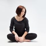 Young beautiful woman sitting in lotus position Royalty Free Stock Images