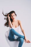 Young beautiful woman sitting on modern chair hair in the wind. Stock Photos