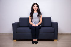 Young beautiful woman sitting on modern sofa at home Stock Photography