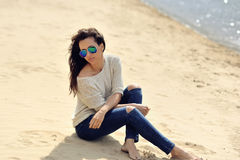 Young beautiful woman sitting near a beach Royalty Free Stock Photography