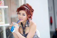 Young beautiful woman sitting at outdoor cafe holding soft drink Stock Photos