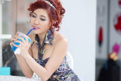 Young beautiful woman sitting at outdoor cafe holding soft drink Royalty Free Stock Photos