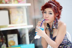 Young beautiful woman sitting at outdoor cafe holding soft drink Stock Images