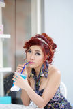 Young beautiful woman sitting at outdoor cafe holding soft drink Royalty Free Stock Images