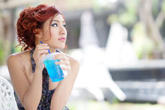 Young beautiful woman sitting at outdoor cafe holding soft drink Royalty Free Stock Photo