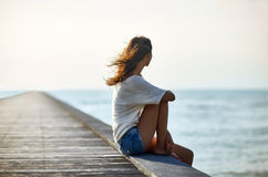 Young beautiful woman sitting on the pier Royalty Free Stock Image