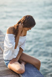 Young beautiful woman sitting on the pier. With copy space royalty free stock photo