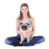 Young beautiful woman sitting with pug dog isolated on white. Background Royalty Free Stock Images