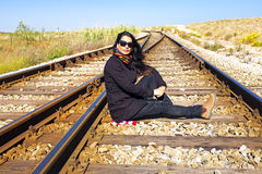 Young beautiful woman sitting on a railroad Stock Photography