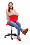 Young Beautiful Woman sitting on red chair Stock Photo