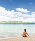 Young beautiful woman is sitting on sand by the se Royalty Free Stock Photos