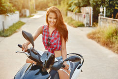 Young beautiful woman sitting on a scooter Royalty Free Stock Photos
