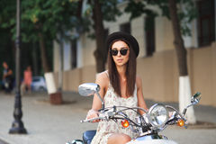 Young beautiful woman sitting on a scooter. Stock Images