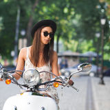 Young beautiful woman sitting on a scooter. Stock Photo
