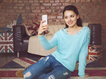 Young beautiful woman sitting with smart phone Royalty Free Stock Images