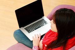 Young beautiful woman sitting on the sofa with laptop Royalty Free Stock Image
