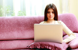 Young beautiful woman sitting on the sofa and using laptop Stock Photography