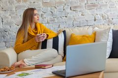 Young beautiful woman is sitting on a sofa on a white brick wall background with a cup of coffee. Laptop, documents Stock Photo