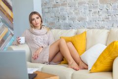 Young beautiful woman is sitting on a sofa on a white brick wall background with a cup of coffee. Laptop, documents Royalty Free Stock Image