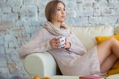 Young beautiful woman is sitting on a sofa on a white brick wall background with a cup of coffee. Laptop, documents Royalty Free Stock Images