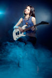 Young beautiful woman is sitting on stage with a guitar . Fog on Royalty Free Stock Photography