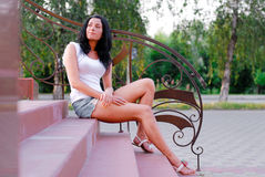 Young beautiful woman sitting on stairs outdoors Royalty Free Stock Photos