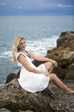 Young beautiful woman sitting on a stone near sea Stock Photography