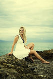 Young beautiful woman sitting on a stone near sea Royalty Free Stock Images