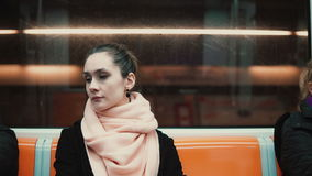 Young beautiful woman sitting in subway. Attractive thoughtful girl goes to work by public transport. Female goes at morning at underground train stock footage