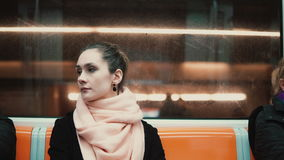 Young beautiful woman sitting in subway. Attractive thoughtful girl goes to work by public transport. Royalty Free Stock Photo